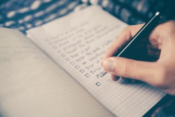 man writing to do list